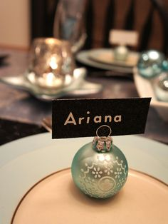 Simple Settings: Designer Katrina Giles used robin's egg blue ornament balls as name card holders for each place setting. The name cards are made of black glitter yardstick and silver letter stickers and can be used from season to season. table settings, holiday parties, place cards, christmas tables, name cards, card holders, place set, ornament place, holiday tables