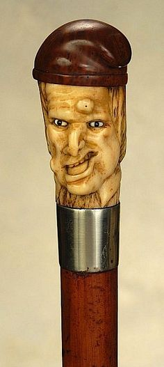 "A fine staghorn cane of a French Revolutionary. The polished staghorn handle is 2 3/4"" high and 1 1/2"" at its widest. It depicts in very nice detail, the face of a French peasant wearing a carved wood Liberty Cap. He has white sulfide eyes and a grotesque countenance with pimpled skin, crooked nose, and mouth held askew. (The cane appears to convey a sly anti-revolution message.) It is perhaps French or English, ca 1880."