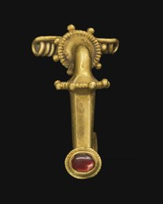A ROMAN GOLD AND GARNET BOW FIBULA   CIRCA 3RD CENTURY A.D.   With an s-shaped bow, round in section and arching along the upper portion, framed above and below by beading and granules, faceted along the length below and tapering, curved out at the end, with a box set cabochon garnet framed by beaded wire, the rectangular catch-plate projecting from the back, a loop at the back of the upper end through which the multi-spiraled spring is threaded, tapering to the long straight pin