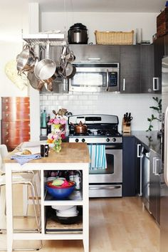Pictured up top is the home of 100 Layer Cake co-creator Amanda Dawnbarn, featured on The Glitter Guide. Her kitchen might be a little bigger than yours, but if you have the same L-shaped configuration, you can do the same thing she did: add an island that provides extra work space, extra storage, and a place for friends to sit and chat while you're making a meal.