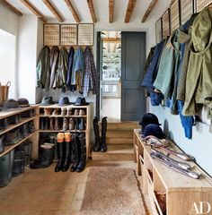The Boot Room features vintage military prints from a Paris flea market alongside coats, hats, and boots for every kind of weather. The limestone flooring came from a quarry on the farm.
