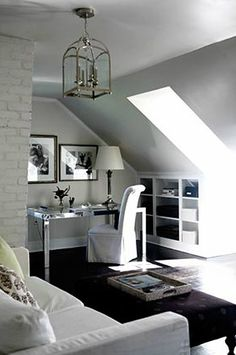 source: Sage Design  Attic office gest bedroom with skylight, gray walls paint, white exposed brick wall, West Elm Parsons Mirror Desk, white slipcover slipper chair, white sofa bed and polished nickel lantern.