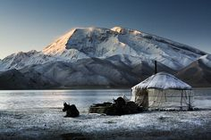 Kyrgyz Yurt, Lake Kara-Kul, Xinjiang. The first rays of sun hit the slopes of Muztagh Ata, 7546m, on the northern edge of the Tibetan Plateau in Xinjiang province near the Pakistan border.