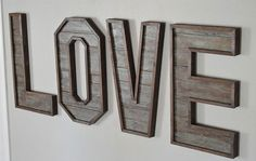 Apply a layer of gray-blue paint onto walnut-stained pallet wood and sand it down to achieve the distinctive coloring of these letters. Get the tutorial at Kruse's Workshop.   - CountryLiving.com