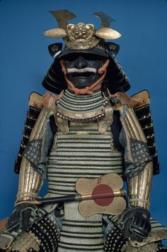 A complete suit of parade armour including interior velvet pockets, a 32-plate helmet with a peak demon crest and a silk banner, Japan, c. 1750 (Edo period). Likely to be a parade piece for a daimyõ. -The Pitt Rivers Museum, Oxford-