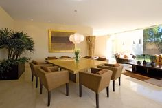 Big scuare dining table with square, leather dining chairs. By Olivia Aldrete Haas
