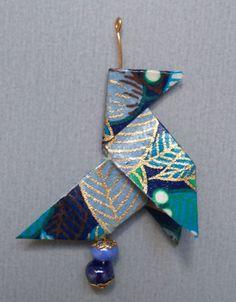 Pendentif cocotte en origami, papier japonais bleu à motifs polychromes de feuilles vertes, bleues, blanches, violettes, rouges et dorées. Le pendentif repose sur une perle bleu - 10425991