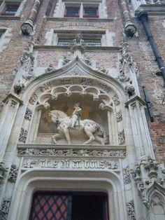 3D sculpture of man on horse in facade of building in Bruges Belgium