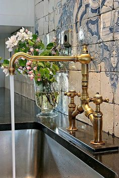 A wall of weathered blue and white tiles, and beautiful faucet!
