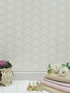 'Skulls' wallpaper by Beware The Moon. The white shimmering glitter wallpaper, symbolising rebirth, features a textured skull and cross bones repeat print.