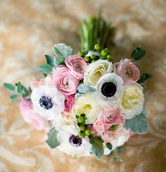 Cream roses, white anemones, light pink ranunculus, green hypericum berries and ornamental eucalyptus make up this light  airy, very feminine bouquet. Via bonnietsangblog.com.