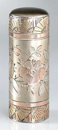 Sterling silver cylinder scent perfume bottle in rose and gold gilt, 1884. Engraved in the Aesthetic manner with a bird in flight, butterfly, flower and leaf spray, as well as rings of fans around the top and base; hinged top and glass stopper