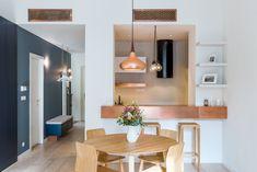 """Kuchyň je s jídelní a obývací části spojena velkým """"podávacím okénkem"""". Měděné prvky dobře ladí s židlemi Malmö od designéra Michala Riabiče a barovkami Rioja (vše TON)."""
