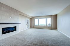 Large family room in basement with custom gas fireplace and mantel