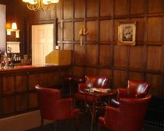 Bury St Edmunds and Farmers Club. Members. Bar. Feature Woodwork. Red. Leather Chairs. Chandelier. Intimate.