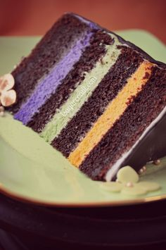 CHOCOLATE LAYER CAKE WITH COLORED BUTTERCREAM :  Butter + Cocoa + Instant espresso powder + Sugar + Sour cream + Almond extract + Eggs + Flour + Baking soda + Salt + Confectioner's sugar + Milk + Vanilla bean + Vanilla extract + Salt + Avocado, Violet and Orange Americolor gel paste
