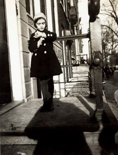 A five year old Anne Frank stands on the steps of her father's office. Amsterdam, 1934.  Photograph by Otto Frank.