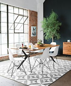Weaver Dining Table + White Alexa Side Chairs. A mid-century inspired table crafted of aged solid oak and metal. The wood's splits, knots and nicks – which occur naturally over time – are one-of-a-kind features that set this stunner apart, and boomerang-shaped legs are as sleek as it gets. #WestsideLoft #LivingSpaces