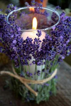Lavender tied to a glass jar with a lit candle inside
