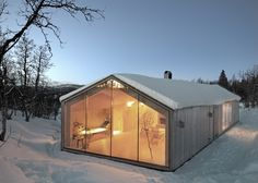 This pine-clad cabin has two glazed gables that frame views of the Norwegian landscape.