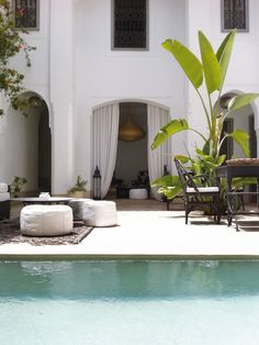 terrasse piscine en pierre blonde, tapis extérieur, poufs design et table ronde