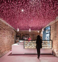 12.000 palos de madera color magenta han servido para hacerle acupuntura al interior de una panadería y pastelería madrileña sin olvidar su pasado