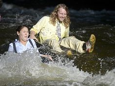 Alyse Kehler, left, and Erik Summerside, right, don their business attire to tube in Boulder Creek for the 7th Annual Tube to Work Day in Boulder, Colorado