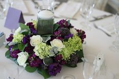 green and purple wedding flowers in centerpiece with candle light by AntebellumDesign.com