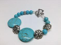 Bracelet #383 ($15)  Bracelet en pierre howlite de couleur bleue et fleurs de métal anti-ternissement, monté sur un fil de métal d'acier inoxydable.   Grandeur 7½ pouces (19 cm). Fait main