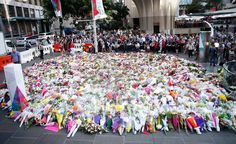 Flowers are placed by people as a mark of respect for the victims of Martin Place siege on December 16, 2014 in Sydney, Australia. Sydney siege gunman Man Haron Monis, was shot dead by police in the early hours of Tuesday morning after taking hostages at the Lindt Chocolat Cafe in Martin Place. Two other people died, 33-year-old cafe manager Tori Johnson and 38-year-old Sydney barrister Katrina Dawson. (Photo by Daniel Munoz/Getty Images)