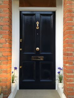 A smart Victorian front door in Farrow & Ball 'Railings' with gleaming, unlacquered brass hardware
