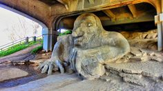 Fremont Troll in Seattle The Fremont Troll is a 18-feet high concrete sculpture located under the north end of the George Washington Memorial Bridge. It is clutching an actual Volkswagen Beetle, bearing California license plate, as if it had just swiped it from the roadway above. Based on the Scandinavian fairy tale Three Billy Goats Gruff, the statue was built by four Seattle area artists for the Fremont Arts Council in 1990, to rehabilitate a particularly unsightly area in the…