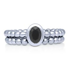 This 2-piece beaded solitaire ring set's vibe is completely contemporary from its dotted bands to its dark, stylish stone. Made of rhodium plated fine 925 sterling silver. Set with 0.43 carat oval cut black cubic zirconia (6mm x 4mm) in bezel setting. Bands measure 4.3mm in width.