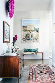 Love this warm + modern entrance hall with a bit of a bohemian flair | Polished concrete floor and warm wood cabinet and bench pair well with the colourful art + rug