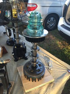 Table lamp made from used car and motorcycle parts. Also has a vintage electrical insulator for the shade and Edison bulb cover. Also has a wooden base that lamp sets on.
