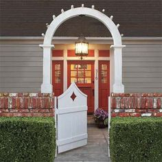 Blueprint for a welcoming entryway: a colorful front door, handsome light fixture centered within an archway atop a brick wall, and perfectly trimmed hedges. | Photo: Mark Lohman | thisoldhouse.com
