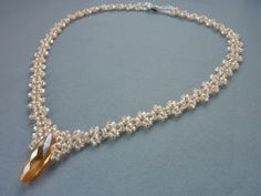 DIY Jewelry: FREE beading pattern for v-shaped necklace made of twin beads and 11/0 seed beads, featuring a drop crystal center component.