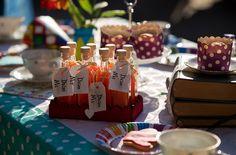 """Bottigliette """"drink me"""" con liquido magico, pile di libri di favole e dolcetti per l'ora del tè"""