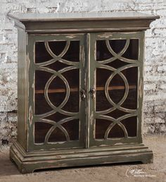Uttermost Duran Console Cabinet. Solid mahogany cabinet finished in hand distressed, glazed charcoal over aged white undertones. Clear glass doors with wooden fretwork encase a honey-stained mahogany interior with adjustable shelf.