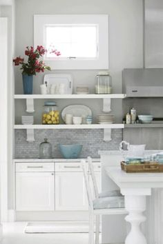 White & Gray Kitchen! White kitchen cabinets, white kitchen island, white kitchen shelves, gray tile kitchen backsplash, stainless steel hood, white kitchen stools with blue upholstered cushions and blue accents! gray paint wall color.