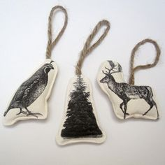 """HISTORIC IMAGES W/MODERN TWIST 19th century engravings of a tree, reindeer and a quail (the closest thing she could find to a partridge:) are digitally printed on organic hemp fabric, backed with cotton canvas and strung with jute twine. Fabulous handmade ornaments coming to us from Canada. All 3 are packaged in a printed cotton gift bag. Approximately 5"""" high each. Bag size: 9"""" x 6"""". Available for a limited time."""