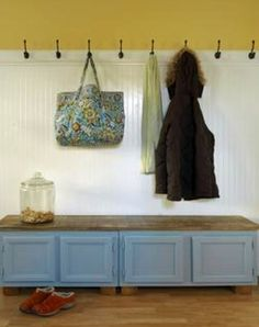 Kitchen wall cabinets, the size normally used above the refrigerator, are topped with a slab of wood to make a mud room bench, complete with storage for very little money