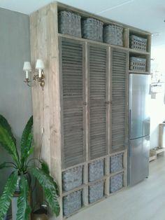 Een stoere wandkast met ingebouwde koelkast. 3 louvre deuren erin....
