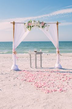 White beach wedding arbor with soft pink accents.
