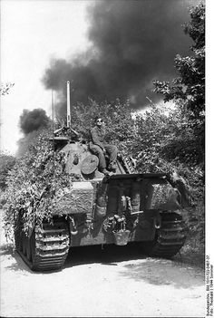 """France -. Camouflaged Panzer V """"Panther"""" with armored soldiers. Black column of smoke in the background; KBZ OB West"""