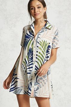 A woven mini shirt dress featuring an allover tropical print, a basic collar, a button front, short dolman sleeves, and a flowy silhouette.