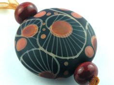 Moogin beads -etched dark amber lentil focal lampwork bead