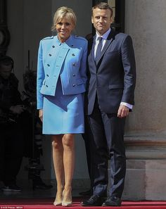 Earlier in the day, he posed for photos at the Elysee palace with his glamorous wife Brigitte (pictured)