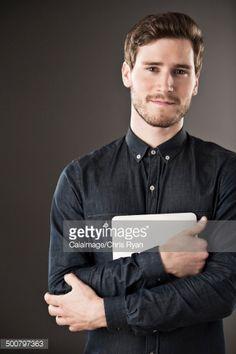 Stock Photo : Portrait of serious businessman holding digital tablet