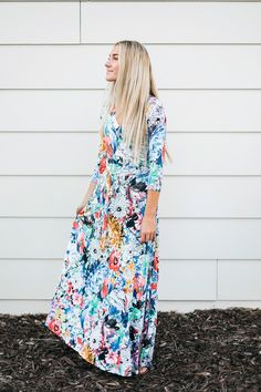 "This faux wrap maxi dress features a bright, watercolor like print, a tie  at the waist, and 3/4 sleeves.  Model is 5'9'' and wearing size Small  Small: Waist: 24""  Length from shoulder to hem: 54""  Medium: 26"" x 55""  Large: 28"" x 56"""